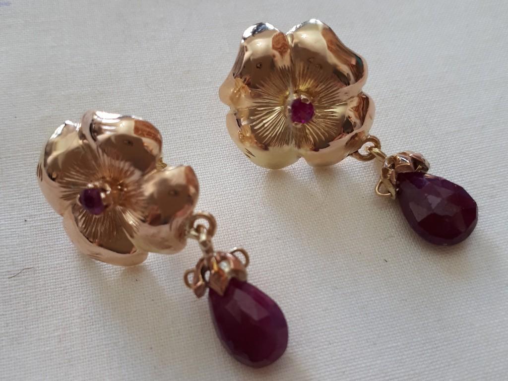 עגילי זהב בעיצוב פרח ועליו תליון רובי